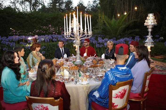 Morocco's King Mohammed VI (CR), his wife Princess Lalla Salma (background L), France's President Emmanuel Macron (CL) and his wife Brigitte Trogneux (background R), attend an Iftar meal, the evening meal when Muslims end their daily Ramadan fast at sunset, at the King Palace in Rabat, Morocco, June 14, 2017. Picture taken June 14, 2017. REUTERS/Abdeljalil Bounhar/Pool