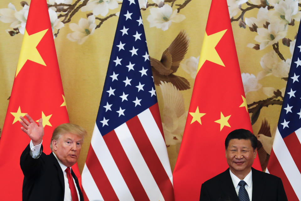 U.S. President Donald Trump waves next to Chinese President Xi Jinping. (Photo: AP Photo/Andy Wong)