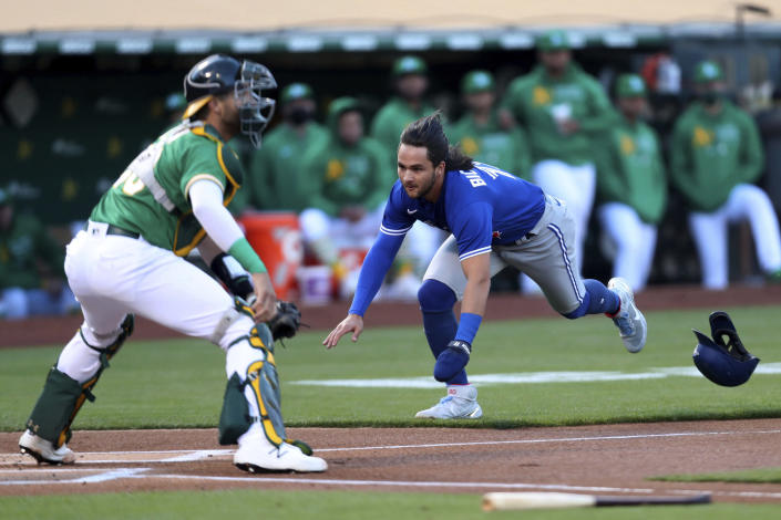 Toronto Blue Jays' Bo Bichette dives for home as Oakland Athletics' Austin Allen waits for the throw during the first inning of a baseball game in Oakland, Calif., Wednesday, May 5, 2021. (AP Photo/Jed Jacobsohn)