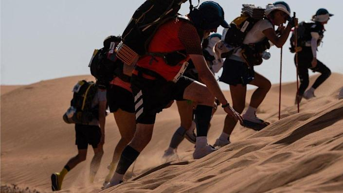 Marathon runners in running gear racing up a sand dune at incline. There are sand dunes in the background as well as relatively clear skies.
