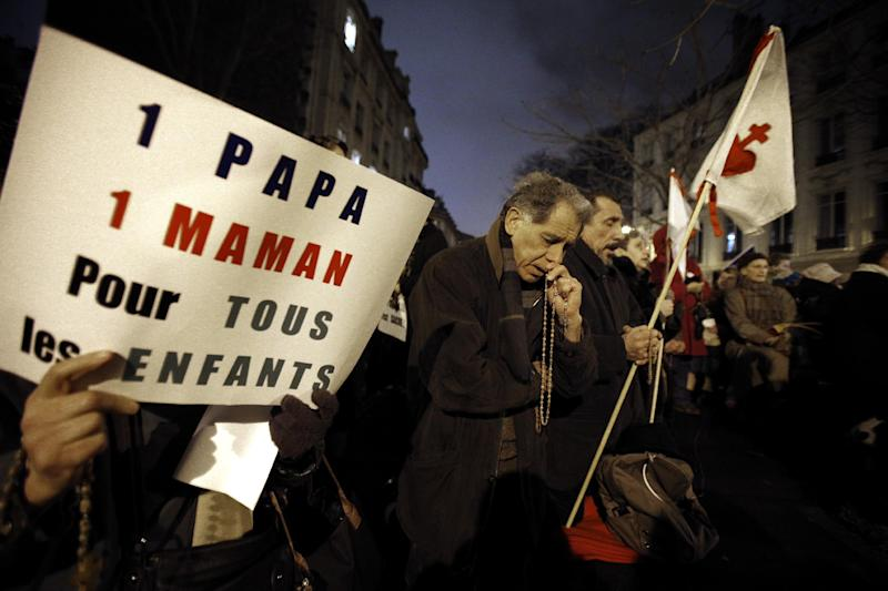"Opponents to gay marriage pray during a demonstration in Paris, Tuesday, Jan. 29, 2013. The French government has presented a divisive plan to legalize gay marriage and adoption to Parliament for debate. The placard reads:  ""One Dad, One Mum for all the Children"". (AP Photo/Christophe Ena)"