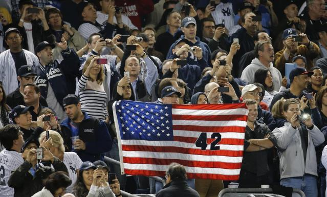 The crowd stands, cheers and takes photos as New York Yankees relief pitcher Mariano Rivera enters the game against the Tampa Bay Rays during the eighth inning of their MLB American League game at Yankee Stadium in New York, September 26, 2013. It was Rivera's final appearance at the Stadium as he is retiring at the end of the season. REUTERS/Ray Stubblebine (UNITED STATES - Tags: SPORT BASEBALL)