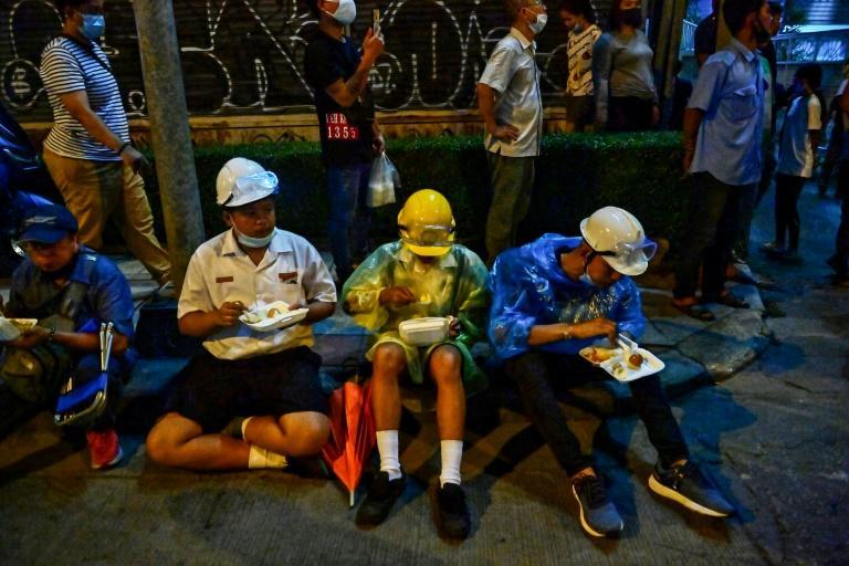 This picture taken on October 21, 2020 shows pro-democracy protesters eating meals from street food vendors during an anti-government rally in Bangkok