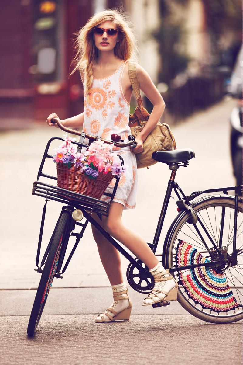 """<div class=""""caption-credit""""> Photo by: freepeople.com</div>A vintage bike with a basket full of flowers and a crochet wheel cozy is a sweet ride."""