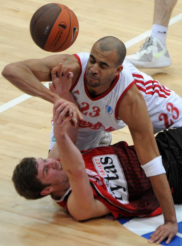 Lietuvos Rytas' Dovydas Redikas vies with BC Spartak Saint-Petersburg's Victor Keyru (top) during Eurocup's Final Four third place basketball match between Lietuvos Rytas and BC Spartak Saint-Petersburg in Khimki, a suburb of Moscow, on April 15, 2012. AFP PHOTO / KIRILL KUDRYAVTSEV