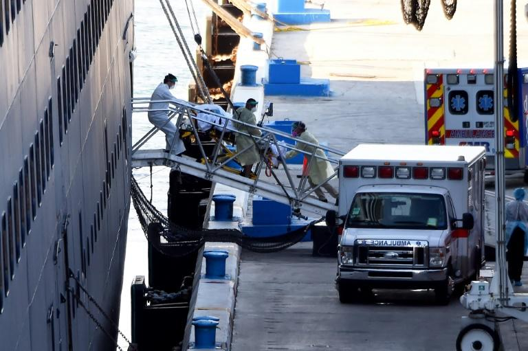 Medics transfer a patient on a stretcher from Holland America's cruise ship Zaandam after it docked at Port Everglades in Fort Lauderdale, Florida