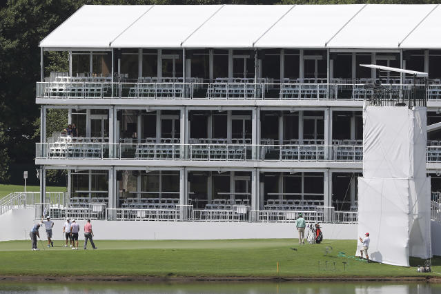 Golfers putt on the 15th green below a three story corporate suite during practice for the Tour Championship golf tournament in Atlanta, Wednesday, Aug. 21, 2019. (Curtis Compton/Atlanta Journal-Constitution via AP)