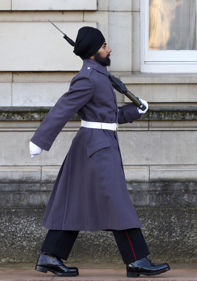 Sikh Guardsman Jatenderpal Singh Bhullar, a soldier in the Scots Guards, marches by his sentry box whilst on guard duty in the forecourt of Buckingham Palace on December 11, 2012 in London, England.  Guardsman Bhullar is the first Sikh Guardsman to wear a turban rather than the traditional bearskin whilst on guard duty. (Photo by Indigo/Getty Images)