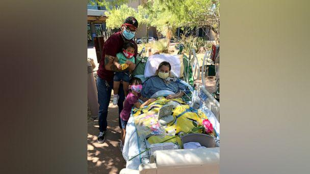 PHOTO: Reyna Lopez poses with her daughters and husband while hospitalized during her recovery from COVID-19. (Courtesy Rodolfo Lopez)