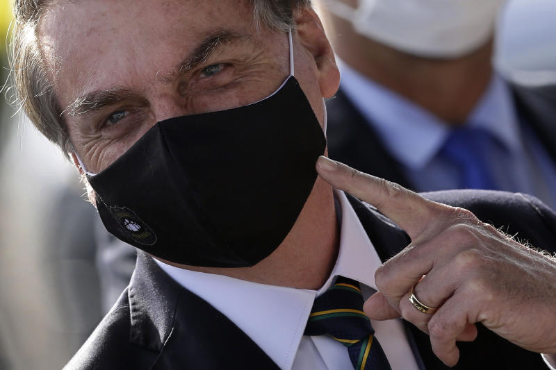 Brazil's President Jair Bolsonaro, wearing a face mask amid the new coronavirus pandemic, speaks to supporters as he leaves his official residence of Alvorada palace in Brasilia, Brazil, Tuesday, May 26, 2020. (AP Photo/Eraldo Peres)