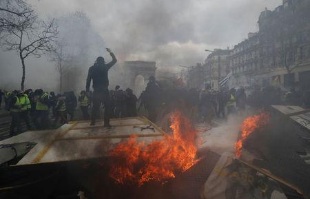 A protester stands on a burning barricade during a demonstration by the