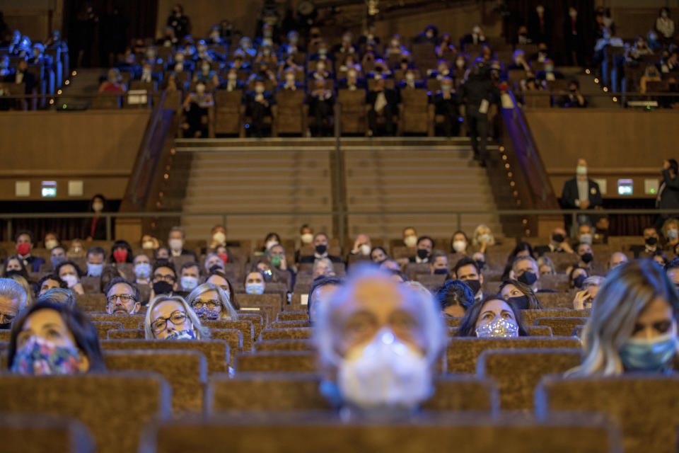 FILE - Guests wear face masks and sit at a safe distance as they follow the opening ceremony of the 77th edition of the Venice Film Festival at Venice Lido, Italy, Wednesday, Sep. 2, 2020. (AP Photo/Domenico Stinellis, File)