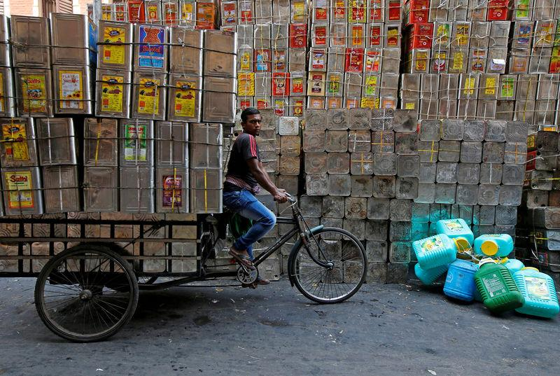 FILE PHOTO: A man pedals a tricycle loaded with empty cooking oil containers in Kolkata