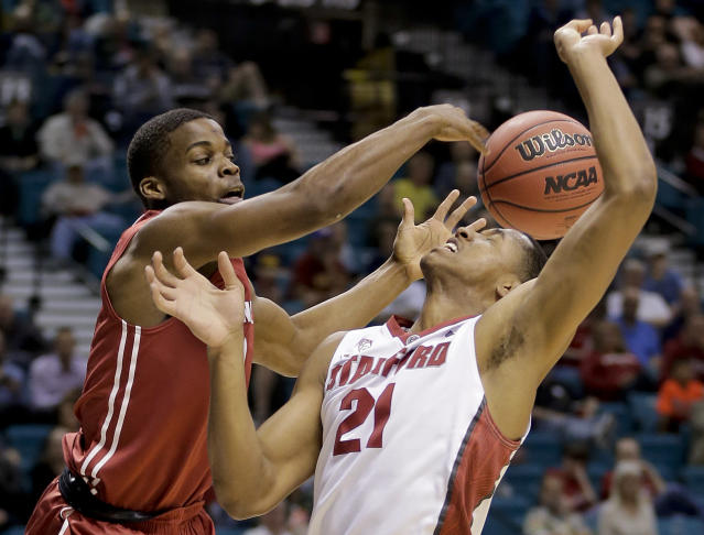 Washington State's Ike Iroegbu, left, fouls Stanford's Anthony Brown in the first half of an NCAA college basketball game in the Pac-12 men's tournament, Wednesday, March 12, 2014, in Las Vegas. (AP Photo/Julie Jacobson)