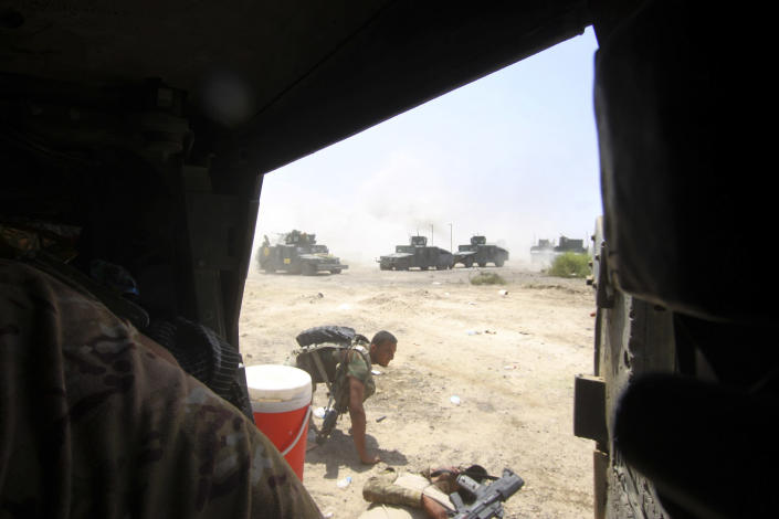 FILE - In this June 15, 2016, file photo, Iraqi security forces prepare to evacuate an injured soldier during heavy fighting against Islamic State group militants in Fallujah, Iraq. The U.S. launched its invasion of Iraq on March 20, 2003, unleashing a war that led to an insurgency, sectarian violence and tens of thousands of deaths. (AP Photo/Anmar Khalil, File)