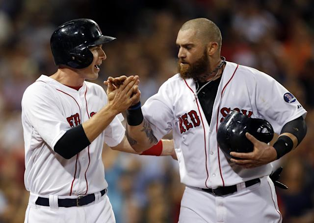 Boston Red Sox's Stephen Drew, left, and Jonny Gomes celebrate after they scored on a single by Will Middlebrooks in the fifth inning of a baseball game against the Detroit Tigers at Fenway Park in Boston, Tuesday, Sept. 3, 2013. (AP Photo/Elise Amendola)