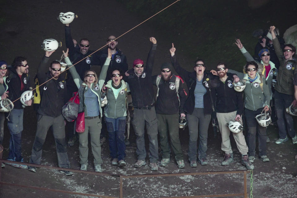 """Members of the French team that participated in the """"Deep Time"""" study, celebrate as they emerge from the Lombrives Cave after 40 days underground in Ussat les Bains, France, Saturday, April 24, 2021.After 40 days in voluntary isolation, 15 people participating in a scientific experiment have emerged from a vast cave in southwestern France. Eight men and seven women lived in the dark, damp depths of the Lombrives cave in the Pyrenees to help researchers understand how people adapt to drastic changes in living conditions and environments. They had no clocks, no sunlight and no contact with the world above. (AP Photo/Renata Brito)"""