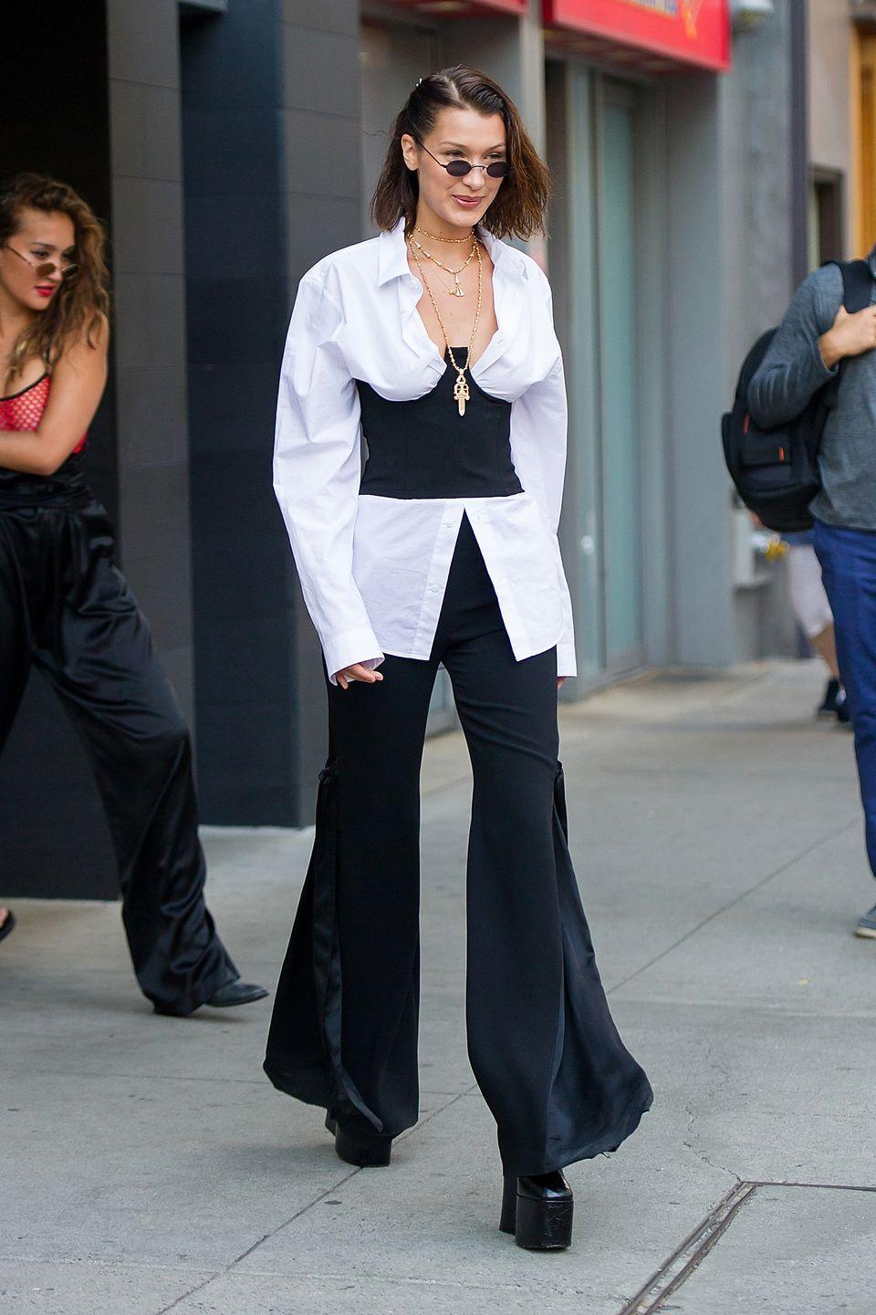 <p>In a white button down, black corset, black wide-leg pants, platform boots, layered gold necklaces and sunglasses while out in New York.</p>