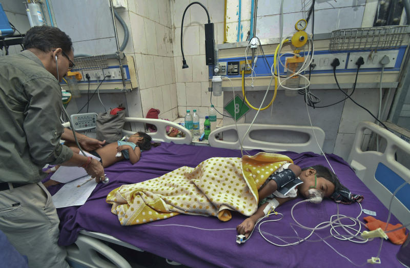 In this Tuesday, June 18, 2019 photograph, a doctor attends to children showing symptoms of acute encephalitis syndrome at Sri Krishna Medical College Hospital in Muzaffarpur, Bihar state, India. More than 100 children have died in an encephalitis outbreak in India's eastern state of Bihar, authorities said Tuesday. (AP Photo/Aftab Alam Siddiqui)