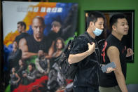 """People walk past a poster for the movie """"Fast & Furious 9"""" at a shopping mall in Beijing, Wednesday, May 26, 2021. Pro-wrestling champion and actor John Cena is apologizing after calling Taiwan a country in promotional interviews for his upcoming film """"Fast & Furious 9."""" (AP Photo/Mark Schiefelbein)"""