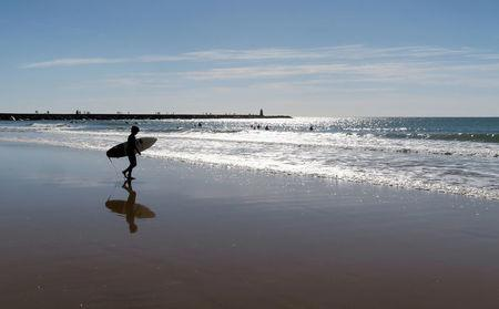 FILE PHOTO: A young surfer is reflected on the wet sand before entering the Atlantic Ocean on the Praia da Rocha beach in Portimao, Portugal, November 6, 2016.   REUTERS/John Schults/File Photo