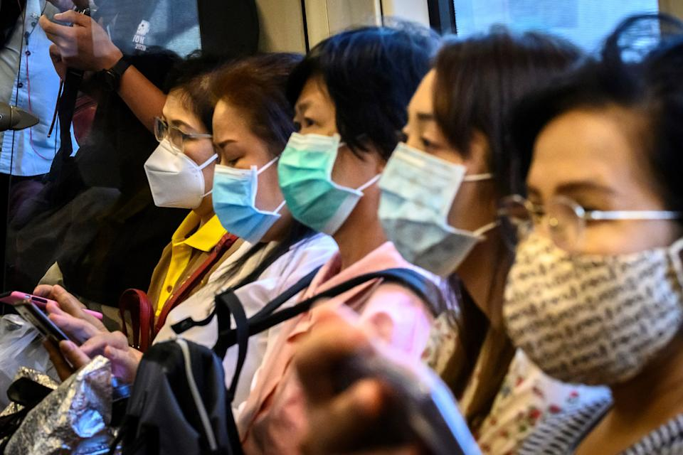 Commuters wearing facemasks amid fears of the spread of the COVID-19 novel coronavirus ride a train in Bangkok on March 9, 2020. (Photo by Mladen ANTONOV / AFP) (Photo by MLADEN ANTONOV/AFP via Getty Images)