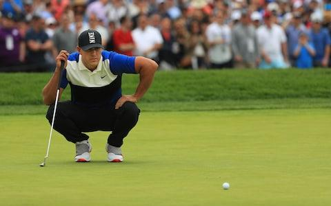 Brooks Koepka gets down to line up his putt on the 1st group - Credit: Getty Images North America