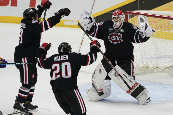 St. Cloud State goaltender David Hrenak, right, celebrates with Nolan Walker (20) and Seamus Donohue after the team's 5-4 wi over Minnesota State in an NCAA men's Frozen Four hockey semifinal in Pittsburgh, Thursday, April 8, 2021. (AP Photo/Keith Srakocic)