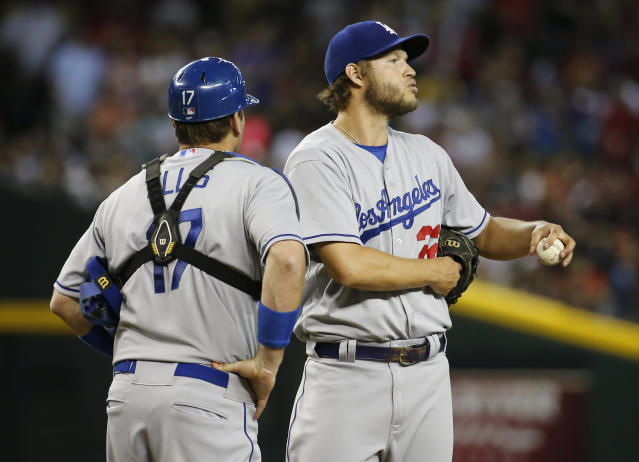Los Angeles Dodgers pitcher Clayton Kershaw, right, looks away as catcher A.J. Ellis walks to the mound during the second inning of a baseball game against the Arizona Diamondbacks on Saturday, May 17, 2014, in Phoenix. Kershaw was pulled form the game in the second. (AP Photo/Matt York)