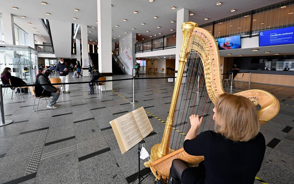 Harpist Sarah Christ performs in a COVID-19 rapid test centre which is located in the Palace of Culture amid the coronavirus pandemic - REUTERS/Matthias Rietschel