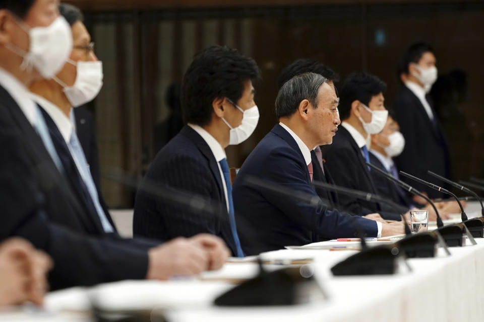 Japanese Prime Minister Yoshihide Suga, center right, attends a government task force meeting for the COVID-19 measures at the prime minister's office Friday, April 9, 2021, in Tokyo. Japan announced Friday that it will raise the coronavirus alert level in Tokyo to allow tougher measures to curb the rapid spread of a more contagious variant ahead of the Summer Olympics. (AP Photo/Eugene Hoshiko, Pool)