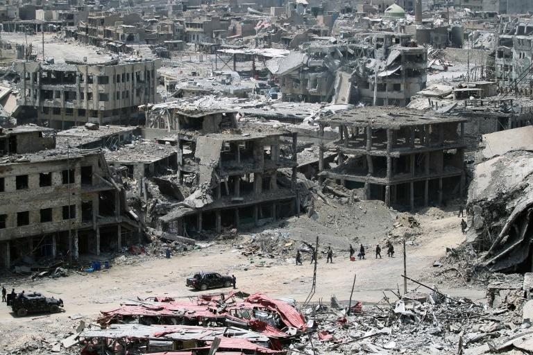 A picture taken on July 9, 2017, shows Iraqi forces walking amidst the destruction in Mosul's Old City