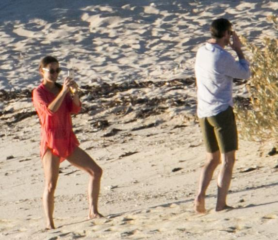 The lovebirds larked around on the beach taking photos of each other.