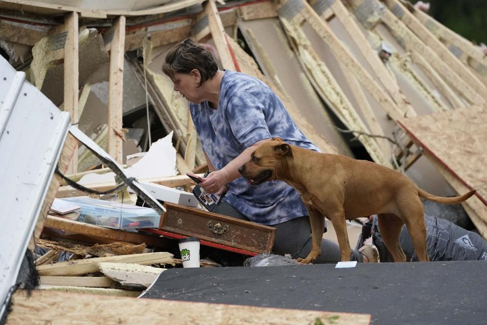 Vickie Savell looks through her belongings amid the remains of her new mobile home early Monday, May 3, 2021, in Yazoo County, Miss. Multiple tornadoes were reported across Mississippi on Sunday, causing some damage but no immediate word of injuries. (AP Photo/Rogelio V. Solis)