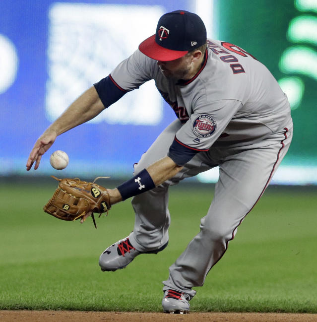 Minnesota Twins second baseman Brian Dozier fields a ball hit by Kansas City Royals' Alcides Escobar during the seventh inning of a baseball game at Kauffman Stadium in Kansas City, Mo., Friday, July 20, 2018. Escobar was safe at first base on the play. (AP Photo/Orlin Wagner)