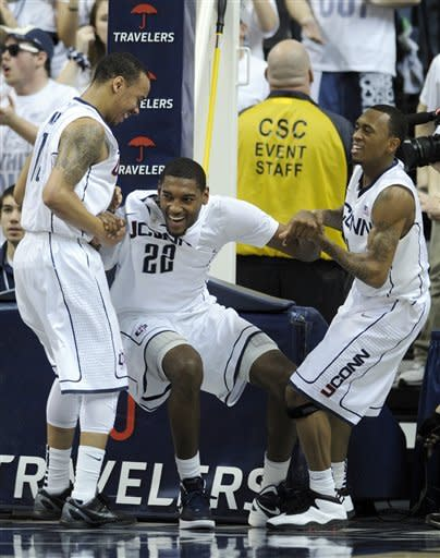 Connecticut's Roscoe Smith, center, is helped up by teammates Shabazz Napier, left, and Ryan Boatright after Smith drew a charging foul late in the second half of Connecticut's 74-65 victory over Pittsburgh in an NCAA college basketball game in Storrs, Conn., on Saturday, March 3, 2012. (AP Photo/Fred Beckham)