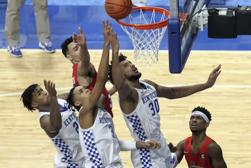 From left to right, Kentucky's Cam'Ron Fletcher watches as B.J. Boston and Olivier Sarr try to tip the ball in as Richmond's Blake Francis looks on during the second half of an NCAA college basketball game in Lexington, Ky., Sunday, Nov. 29, 2020. (AP Photo/James Crisp)