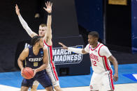 Oral Roberts' Kevin Obanor (0) gets pressure from Ohio State's Justin Ahrens, center, and E.J. Liddell (32) during the first half of a First Round game in the NCAA men's college basketball tournament, Friday, March 19, 2021, at Mackey Arena in West Lafayette, Ind. (AP Photo/Robert Franklin)