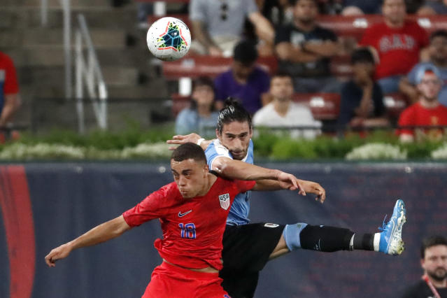 United States' Sergino Dest, left, and Uruguay's Martin Caceres leap after a loose ball during the first half of a friendly soccer match Tuesday, Sept. 10, 2019, in St. Louis. (AP Photo/Jeff Roberson)