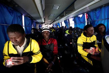 FILE PHOTO: Illegal African migrants sit in a bus before their voluntary return to their countries, in Tripoli