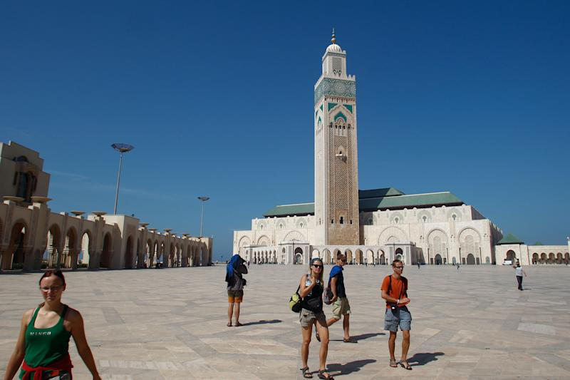 In this Sunday, Oct. 7, 2012 photo, tourists walk in front of Casablanca, Morocco's Hassan II mosque, one of the biggest mosques in the world. Inaugurated in 1992, it's a splendid example of traditional Moroccan architecture. Casablanca, a bustling city of 4 million and the county's commercial capital, is a vibrant mix of old and new with art-deco architecture, traditional souqs and beaches. (AP Photo/Abdeljalil Bounhar)