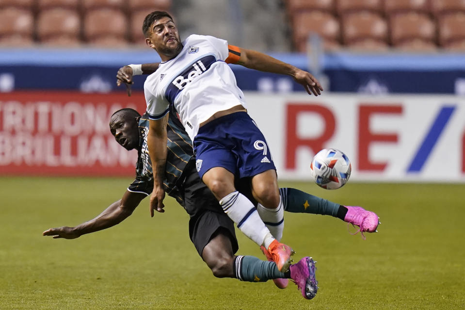 Los Angeles Galaxy S. Coulibaly, rear, and Vancouver Whitecaps forward Lucas Cavallini (9) battle for the ball in the first half during an MLS soccer match Wednesday, June 23, 2021, in Sandy, Utah. (AP Photo/Rick Bowmer)