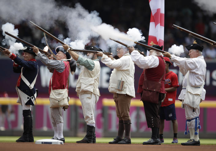 Men dressed as Revolutionary War soldiers fire a volley prior to the national anthem before the baseball game between the Atlanta Braves and Miami Marlins Sunday, July 4, 2021, in Atlanta. (AP Photo/Ben Margot)