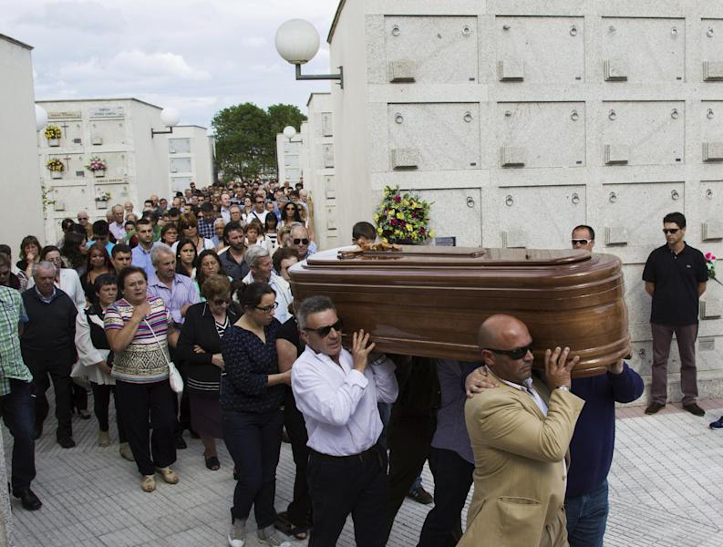 People carry a coffin of a medical student, Laura Naveiras Ferreiro, one of the train crash victim, during her funeral at the San Pedro de Visma cementery in A Coruna, Spain, Saturday, July 27, 2013. Spain's interior minister Jorge Fernandez Diaz says the driver whose speeding train crashed, killing 78 people, is now being held on suspicion of negligent homicide. The Spanish train derailed at high speed Wednesday killing 78 and injuring dozens more. (AP Photo/Lalo R. Villar)