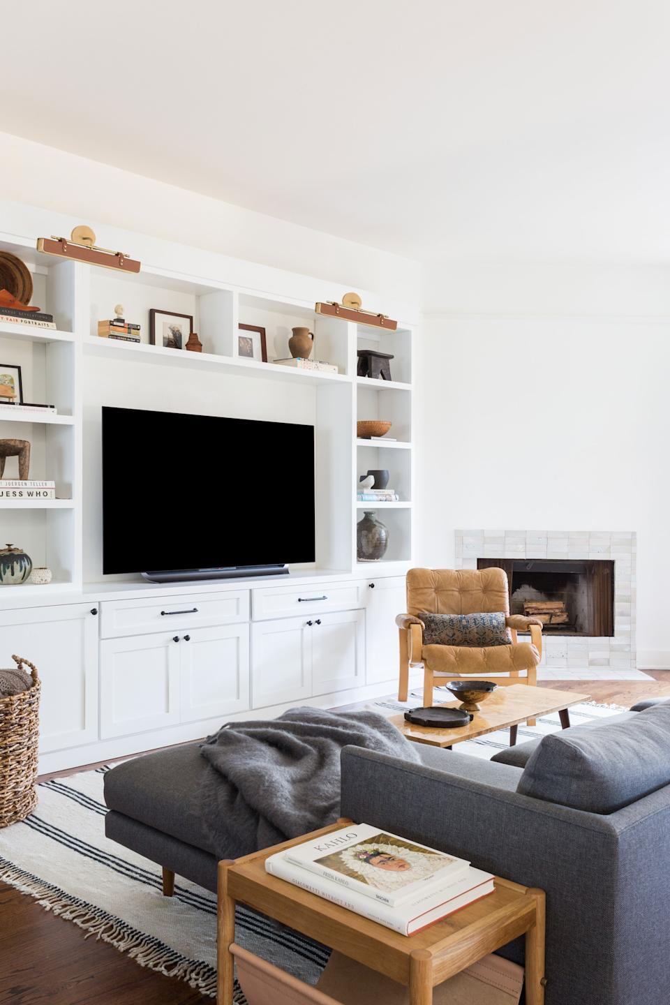 "<div class=""caption""> The first floor of the home is essentially one large space, but the family room acts as a cozy gathering spot. The couch is from <a href=""https://www.article.com/"" rel=""nofollow noopener"" target=""_blank"" data-ylk=""slk:Article"" class=""link rapid-noclick-resp"">Article</a>, the chair is a vintage Bruno Mathsson, and the rug is from <a href=""https://shoppe.amberinteriordesign.com/"" rel=""nofollow noopener"" target=""_blank"" data-ylk=""slk:Shoppe Amber Interiors"" class=""link rapid-noclick-resp"">Shoppe Amber Interiors</a>. The built-ins were custom designed by ABD. </div>"