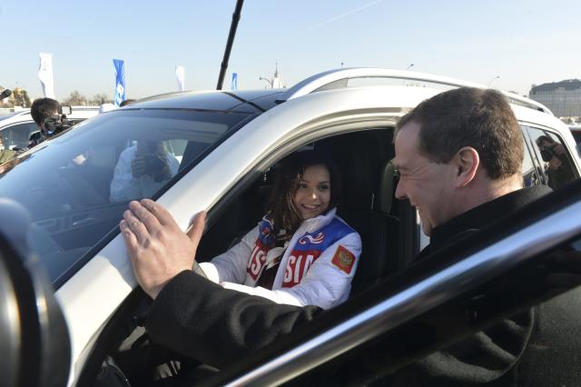 Russia's Prime Minister Dmitry Medvedev and figure skating gold medal winner Adelina Sotnikova attend a ceremony to present automobiles to the Sochi 2014 Winter Olympics prize-holders representing Russia, by the Kremlin wall in central Moscow, February 27, 2014. REUTERS/Artem Zhitenev/RIA Novosti/Pool (RUSSIA - Tags: POLITICS SPORT OLYMPICS) ATTENTION EDITORS - THIS IMAGE HAS BEEN SUPPLIED BY A THIRD PARTY. IT IS DISTRIBUTED, EXACTLY AS RECEIVED BY REUTERS, AS A SERVICE TO CLIENTS