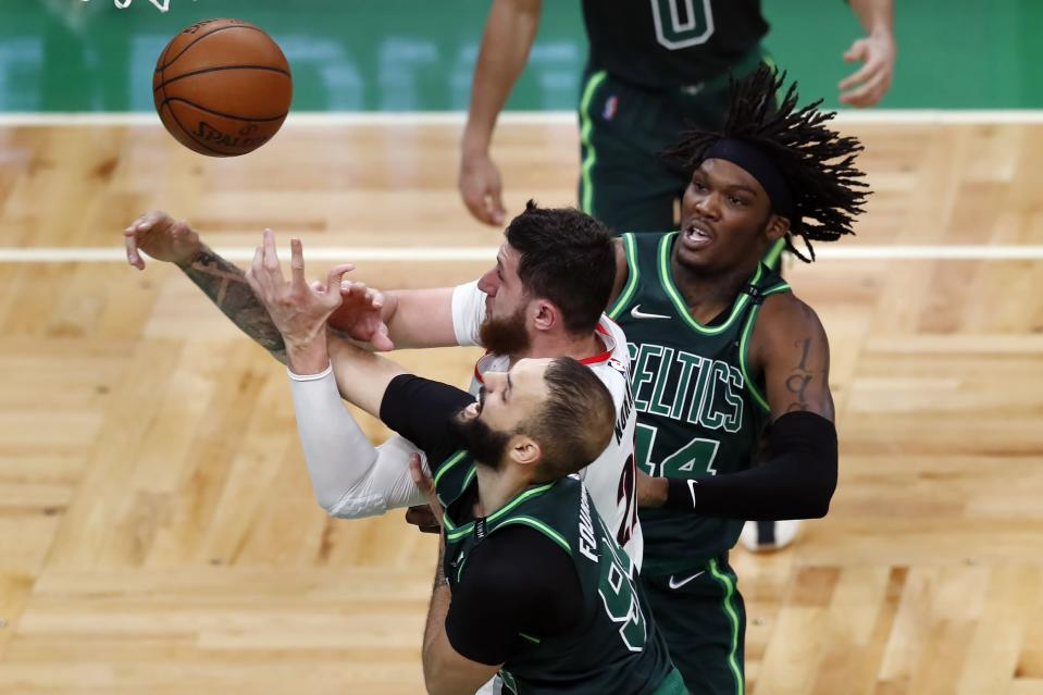 Boston Celtics' Evan Fournier (94) and Robert Williams III (44) battle Portland Trail Blazers' Jusuf Nurkic (27) for a rebound during the second half of an NBA basketball game, Sunday, May 2, 2021, in Boston. (AP Photo/Michael Dwyer)