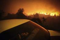 In this image released by World Press Photo, Thursday April 15, 2021, by Nuno Andre Ferreira, Agencia Lusa, titled Forest Fire, which won third prize in the Spot News Singles category, shows A child sits inside a car close by a forest fire in Oliveira de Frades, Portugal, on Sept. 7, 2020. (Nuno Andre Ferreira, Agencia Lusa, World Press Photo via AP)