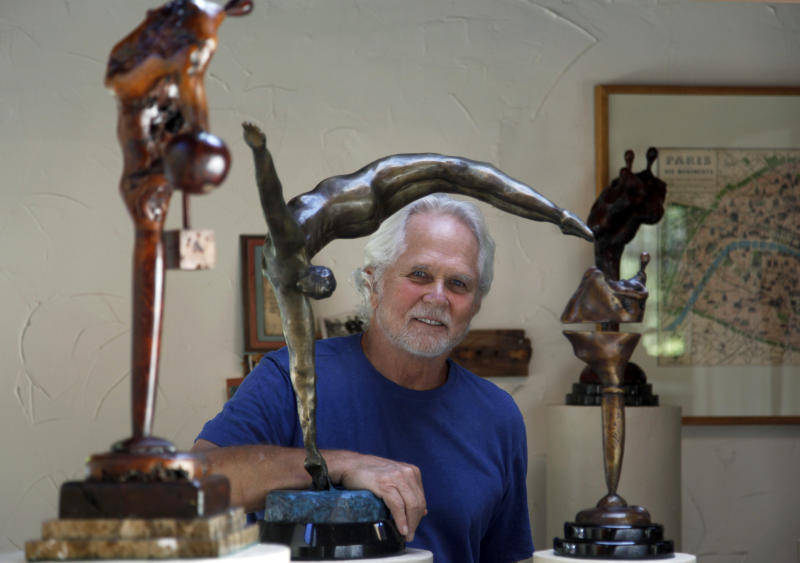"""In this Thursday, Sept. 18, 2012 photo, Tony Dow, actor, director and artist, poses with, from left, Adam's Rib, Half Twist and Waiting, at his home and studio in the Topanga area of Los Angeles. When it comes time to sitting down in a studio and carving out bronze and wooden sculptures inspired by the nature all around him, Wally isn't leaving it up to the Beav these days. Dow, who famously played the Beaver's older brother Wally on the classic 1950s-60s sitcom """"Leave it To Beaver,"""" is carving out a name for himself in the art world these days, as an abstract artist. (AP Photo/Reed Saxon)"""