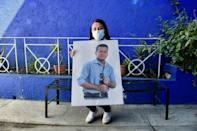 Yesenia Leyva holds a picture of her late husband Christian Cruz, one of several thousand Mexican health workers killed by Covid-19